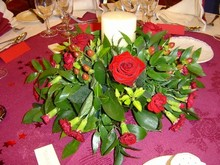 Table centre arrangement with candle in reds and greens